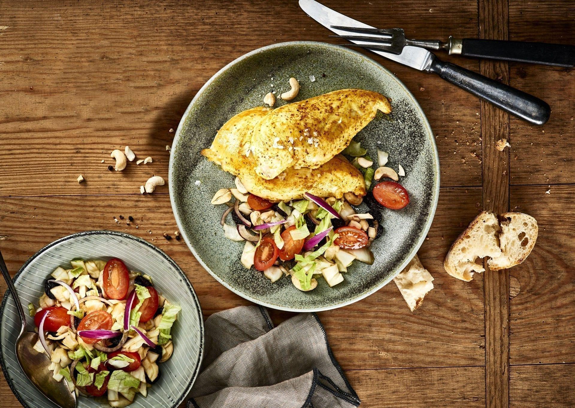 Sprød bagt kyllingebryst serveret med frisk salat og brød